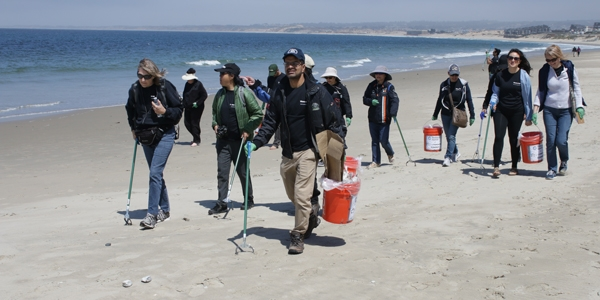 A group of volunteers cleans up trash and debris on California's Del Monte Beach.