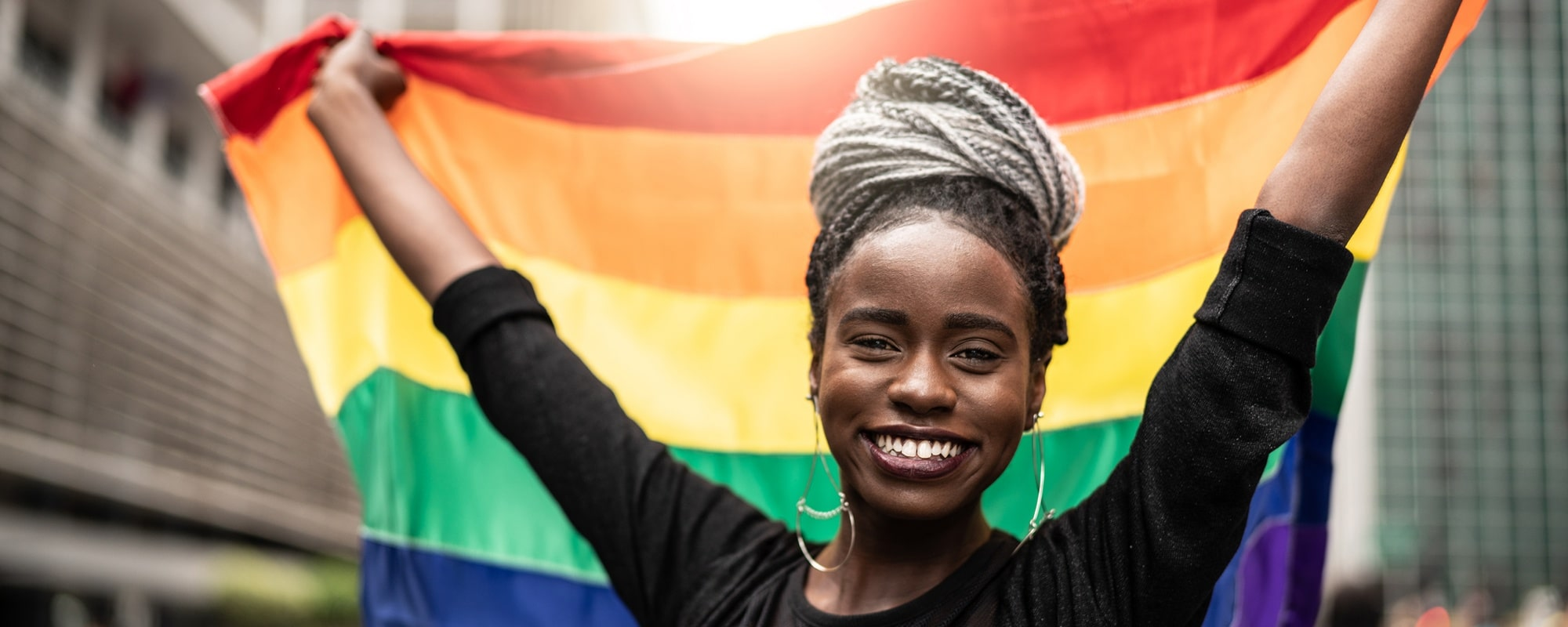 A cheerful woman holds up a rainbow flag in solidarity with Pride Month.