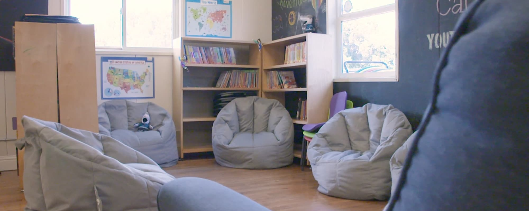 Bright classroom corner outfitted with filled bookshelves, maps, and bean bag chairs.