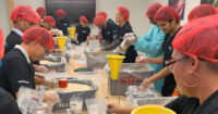 Western Digital employees pack meals during a volunteer event.