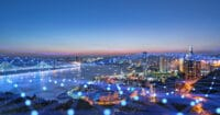 A network of data points overlaid on an illuminated city landscape at night