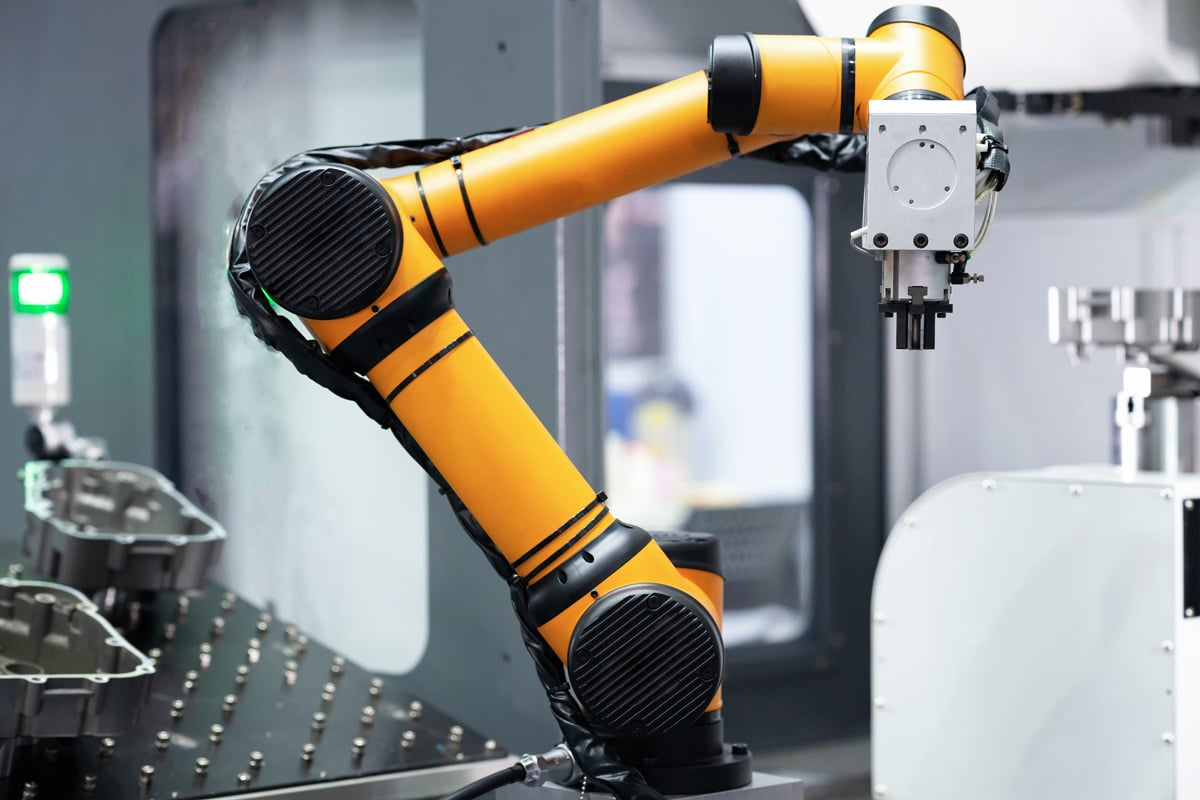 A bright yellow robotic arm appears in a manufacturing facility.