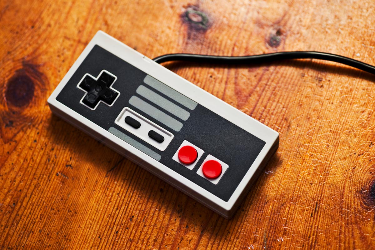 A retro video game controller rests on top of a wooden table
