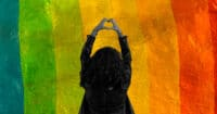 A person holds up a heart sign against a rainbow background.